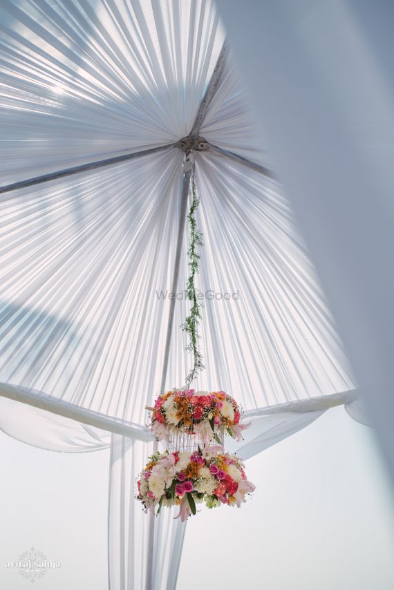 Photo of Floral chandelier hanging from white mandap