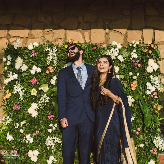 Photo of Engagement decor idea with couple standing against flower wall