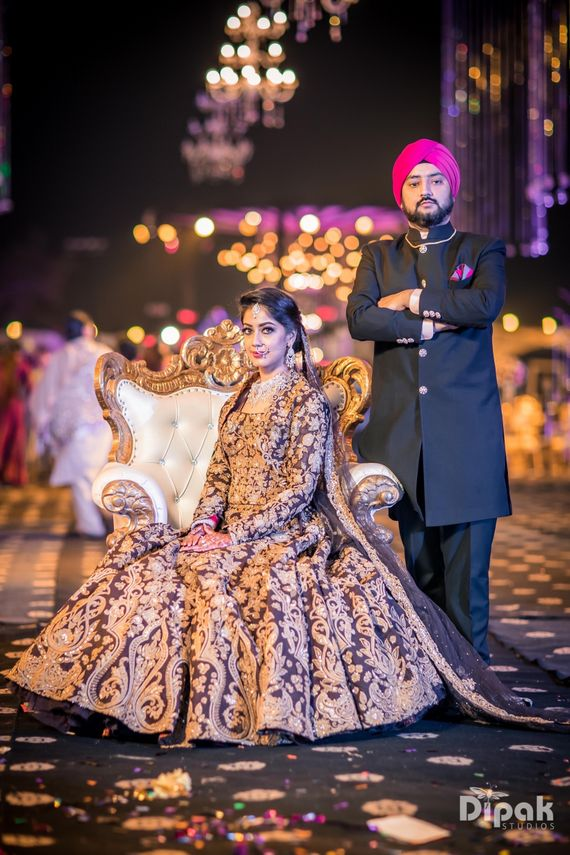 Photo of Maroon and gold heavily embroidered bridal lehenga