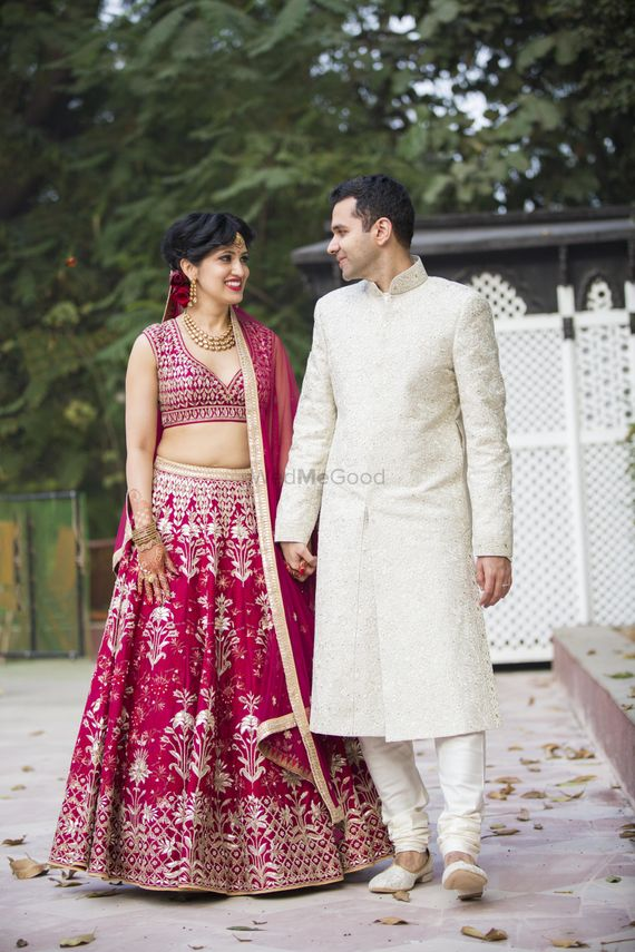 Photo of Matching bride and groom with bride in maroon and groom in white