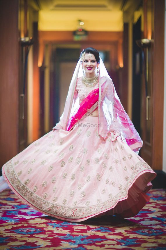 Photo of Bride twirling in light pink lehenga