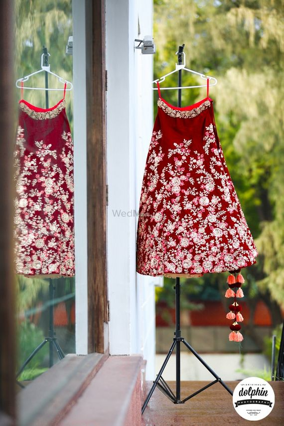 Photo of Maroon velvet bridal lehenga on hanger on tripod