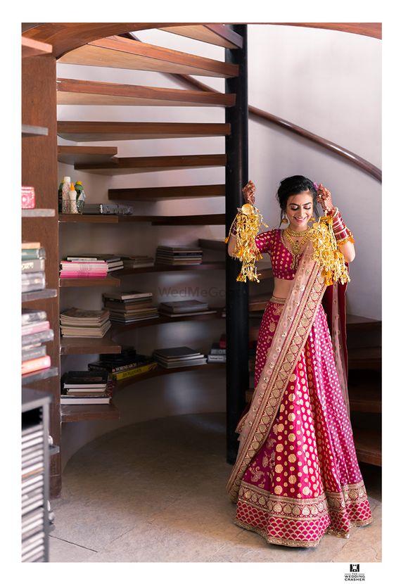 Photo of Bride showing off kaleere in panelled red lehenga