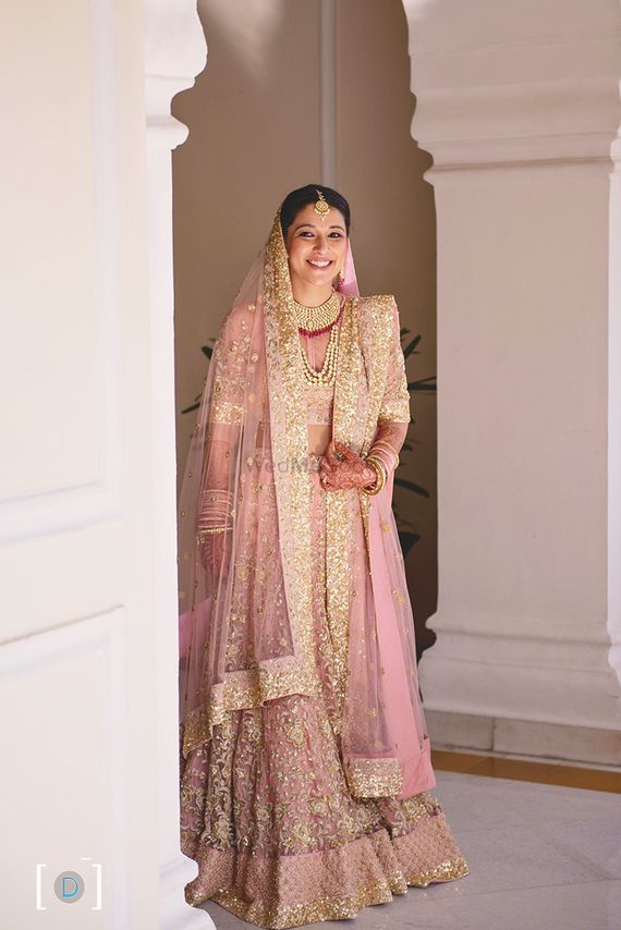 Photo of Shimmery pink pastel pink lehenga with gold sequins