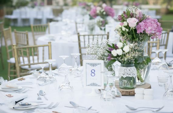 Photo of Gorgeous table setting with white and lavender flowers in glass jars