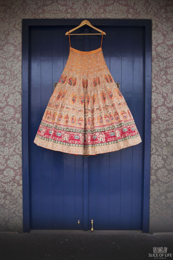 Photo of Yellow and red bridal lehenga on hanger