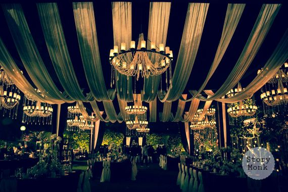 Photo of Night decor with white draped ceiling and candle lit chandeliers