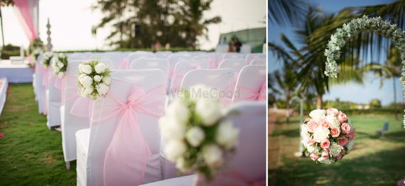 Photo of white chairs with light pink bow and white flower bunch