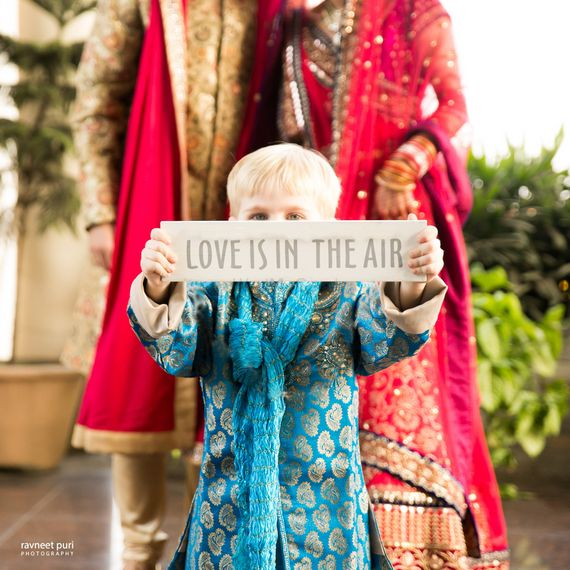 Photo of Couple with kid at wedding holding placard