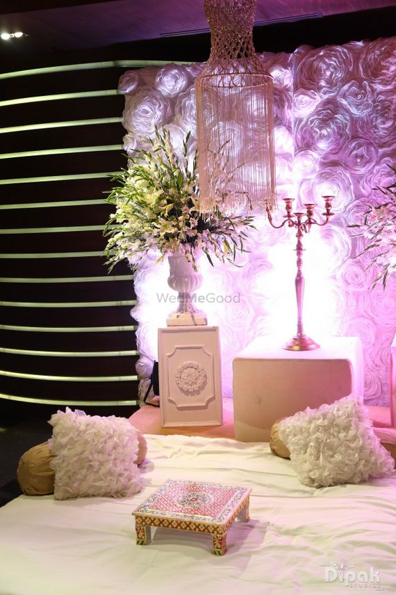 Photo of White and pink low seating idea with furry cushions