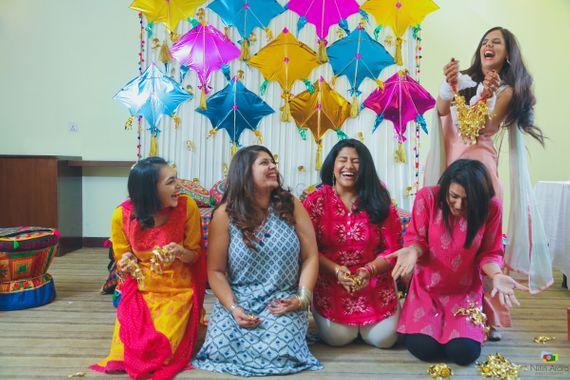 Photo of Bride dropping kaleera on bridesmaid photo