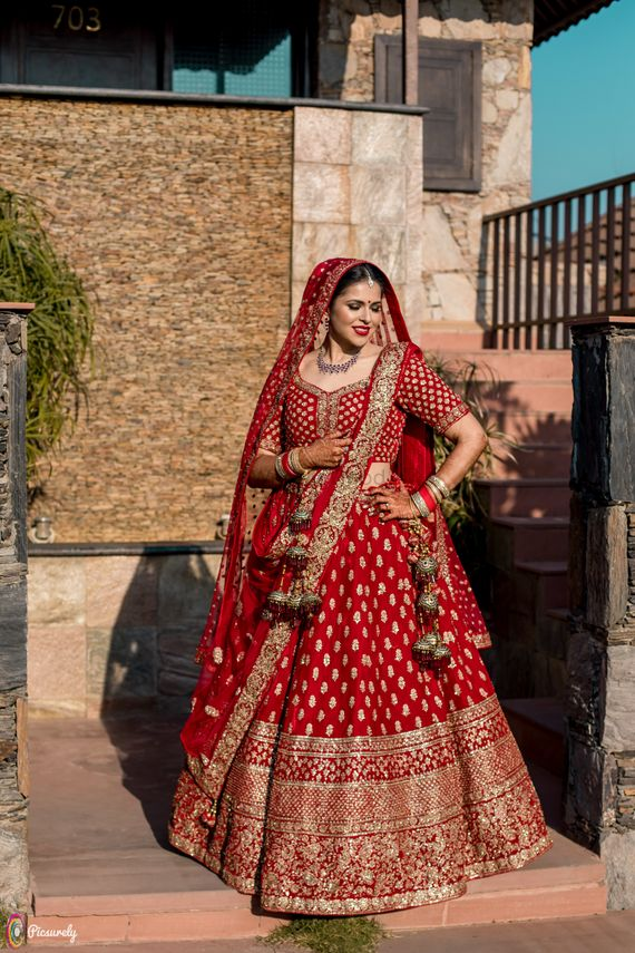 Photo of Red and gold bridal lehenga with unique latkan
