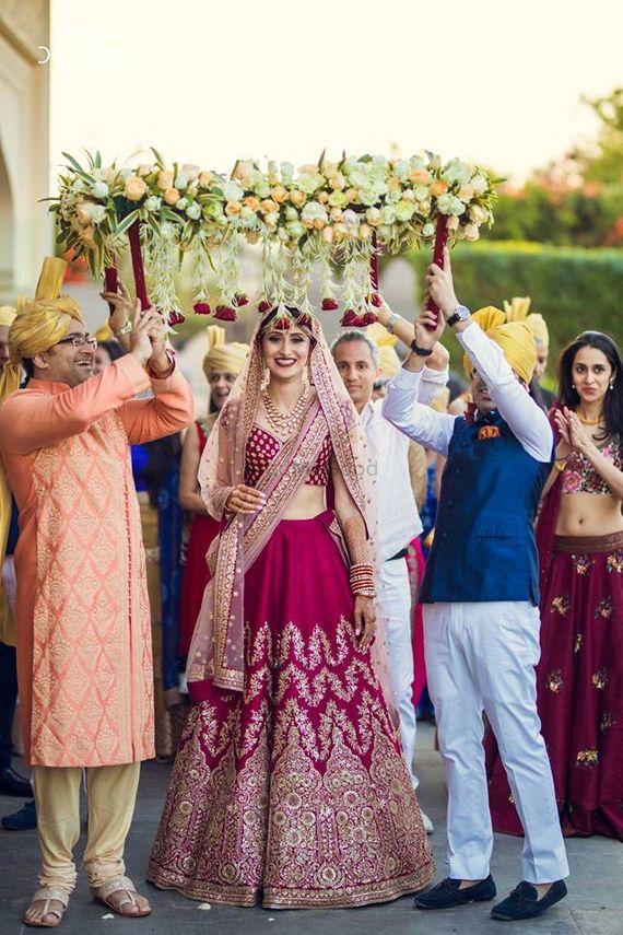 Photo of Bride in maroon lehenga under phoolon ki chadar
