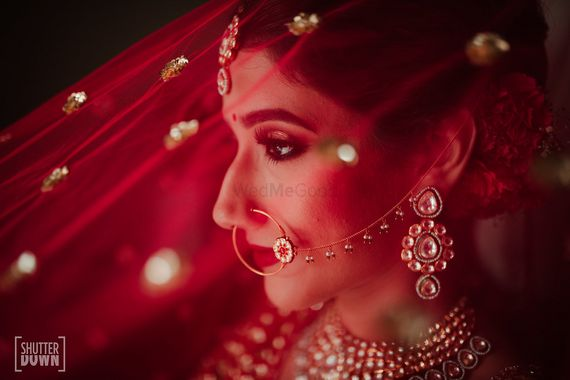 Photo of Bridal portrait with red dupatta as veil