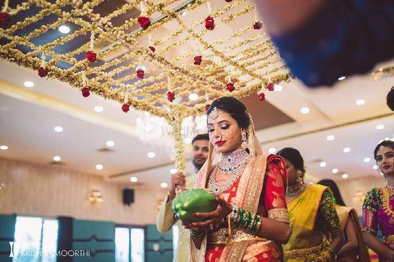 Photo of south indian bridal entry under phoolon ka chadar