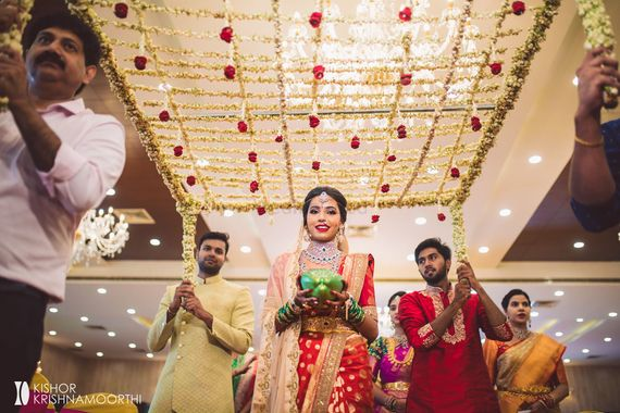 Photo of south indian fusion bridal entry under floral chadar