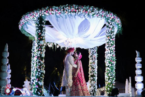 Photo of A bride and groom under a floral mandap.