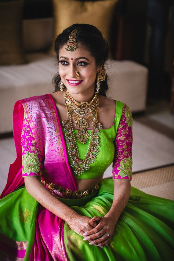 Photo of Mehendi bridal portrait in green and pink lehenga and layered jewellery