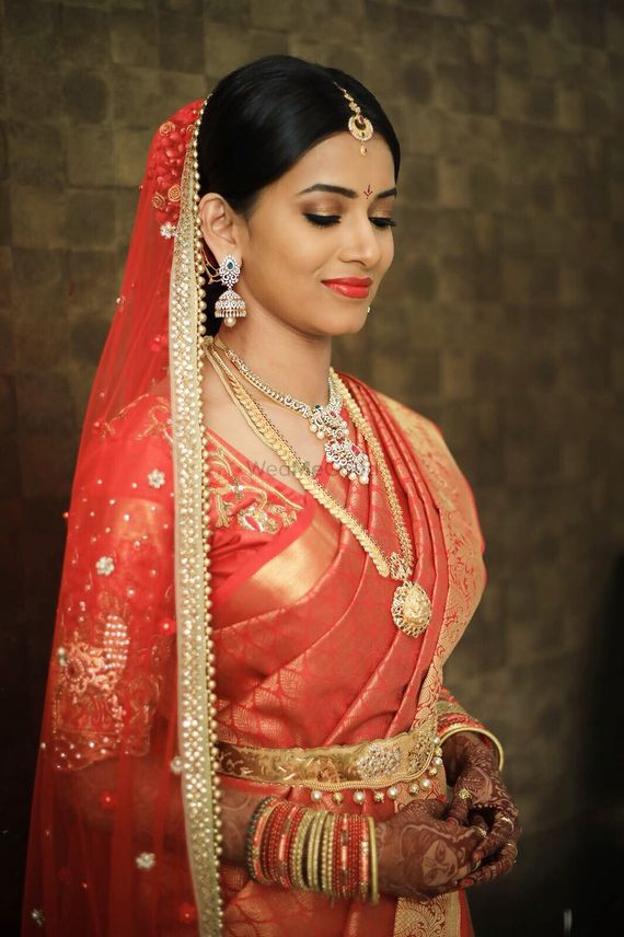 Photo of South Indian bride in orange and gold with simple jewellery