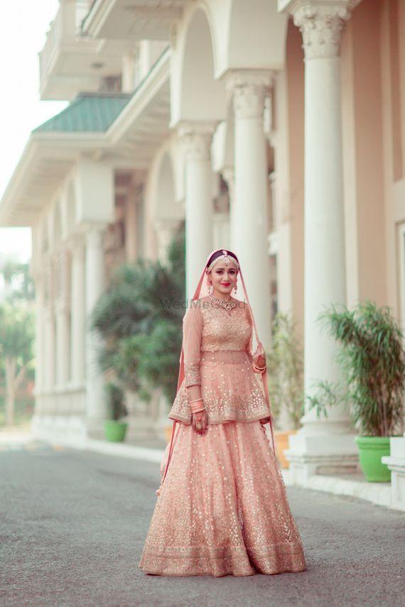 Photo of Unique peach bridal lehenga with peplum blouse