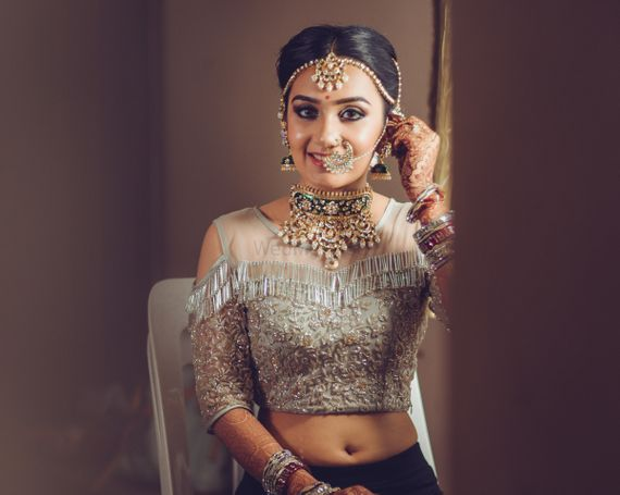 Photo of Indian bride wearing cold shoulder blouse with tassels with unique gold choker necklace