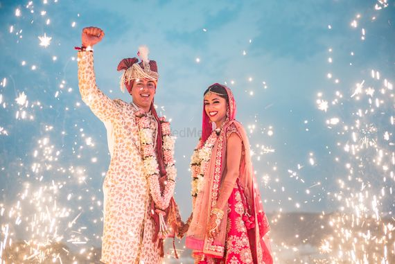 Photo of A bride and groom amidst sparklers