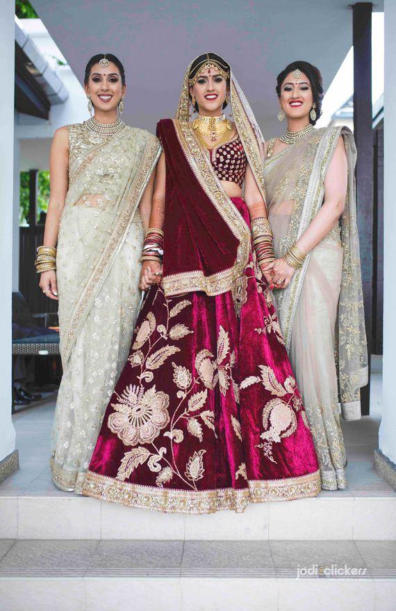 Photo of Bride with sister in velvet lehenga