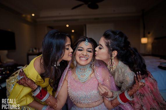 Photo of Cute bridesmaid kissing brides photo