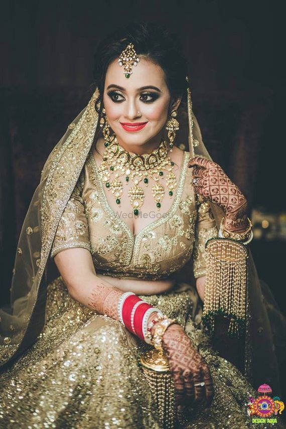 Photo of Bride in gold lehenga with kaleera