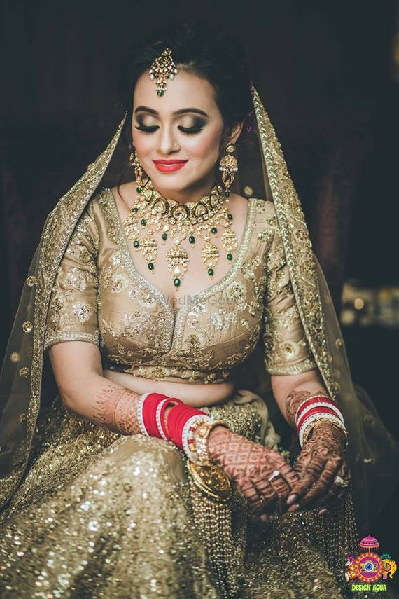 Photo of Monotone gold bridal lehenga with green jewellery