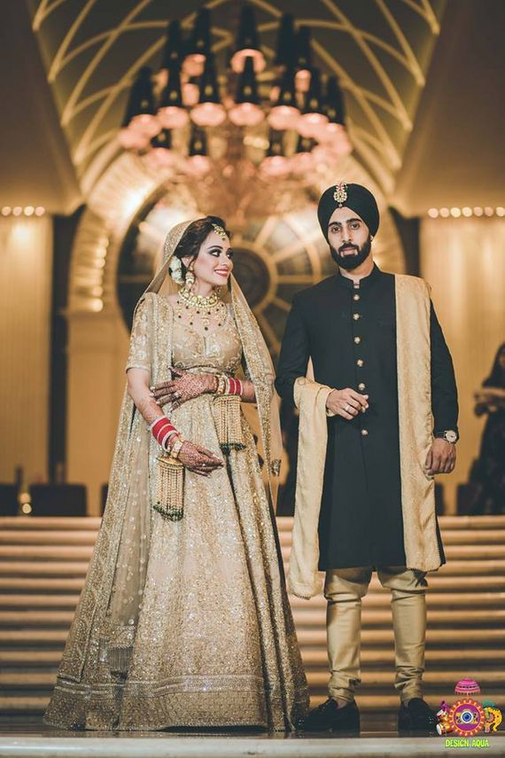 Photo of Contrasting bride and groom in gold and black