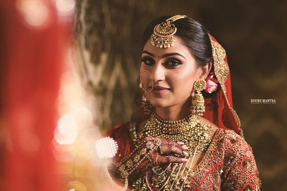 Photo of Bride looking into mirror with heavy bridal jewellery