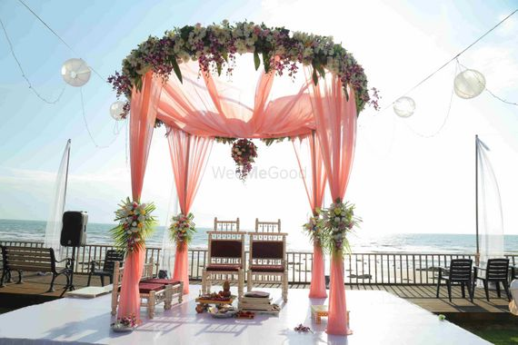 Photo of Round mandap with pastel drapes and florals