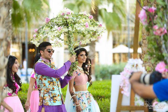Photo of Couple entering floral umbrella on mehendi