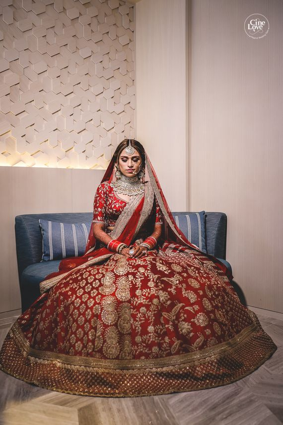 Photo of Bride in deep red and gold lehenga with panels
