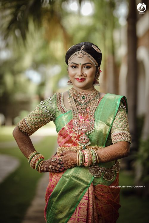 Photo of Beautiful south Indian bride wearing a pistachio and pink saree with jewellery