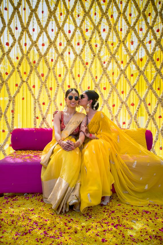 Photo of Two sisters pose together on the haldi ceremony