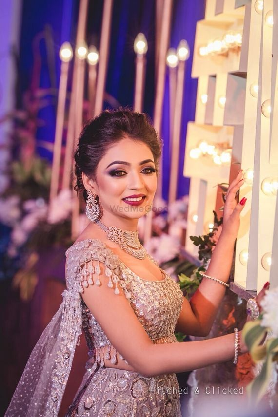 Photo of Bridal makeup with silver lehenga and tassels on sleeves