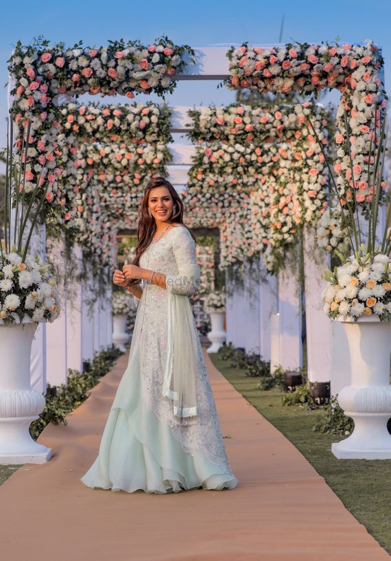 Photo of A bride posing in front of floral entrance decor