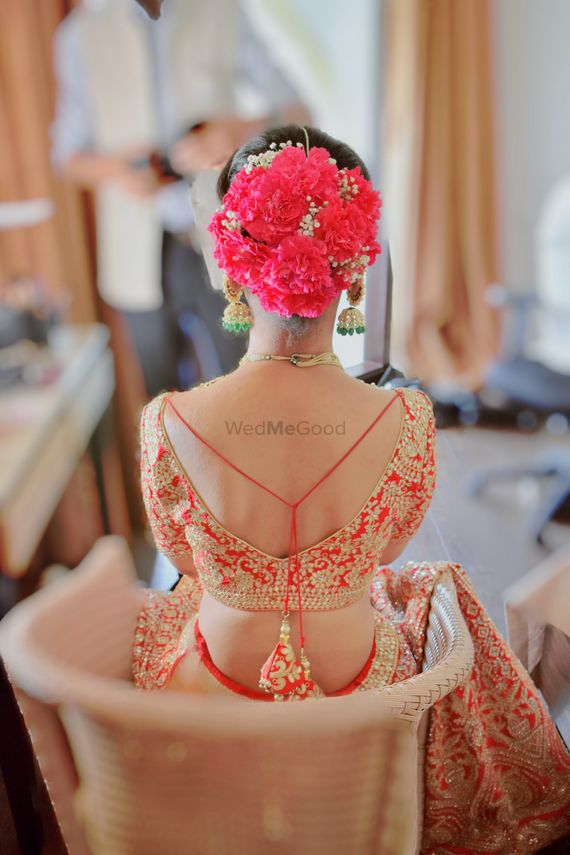 Photo of A bride wearing oversized flowers with baby breath in her bridal bun.