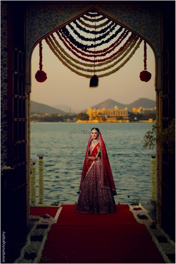 Photo of A bride in a red lehenga poses in front of a lake in Udaipur
