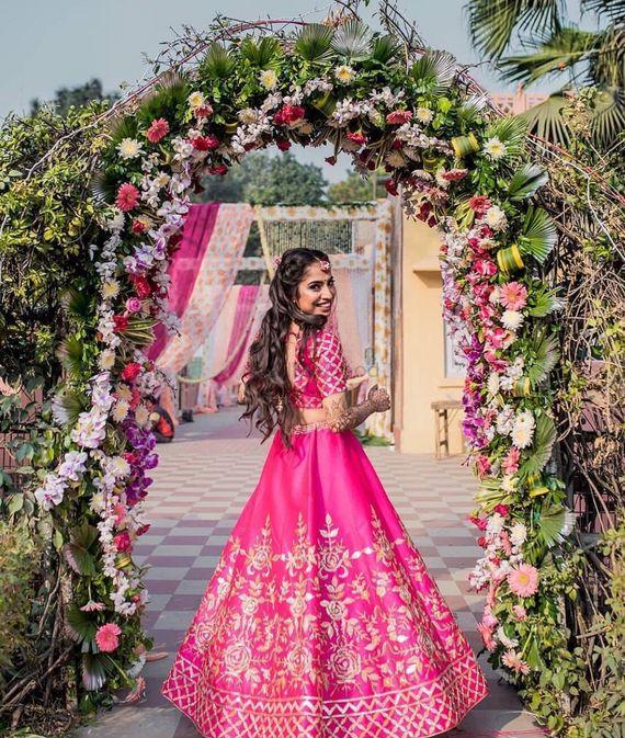 Photo of A bride in a pink lehenga on her mehendi