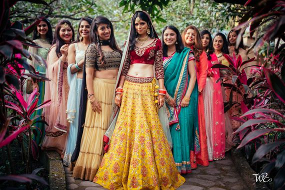 Photo of A bride stands tall with her bridesmaids