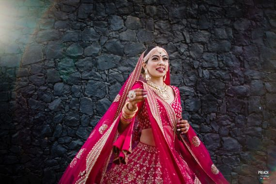 Photo of A happy bride twirling in a beautiful lehenga on her wedding day.