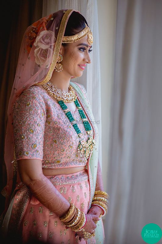 Photo of A bride in pink lehenga with contrasting jewellery