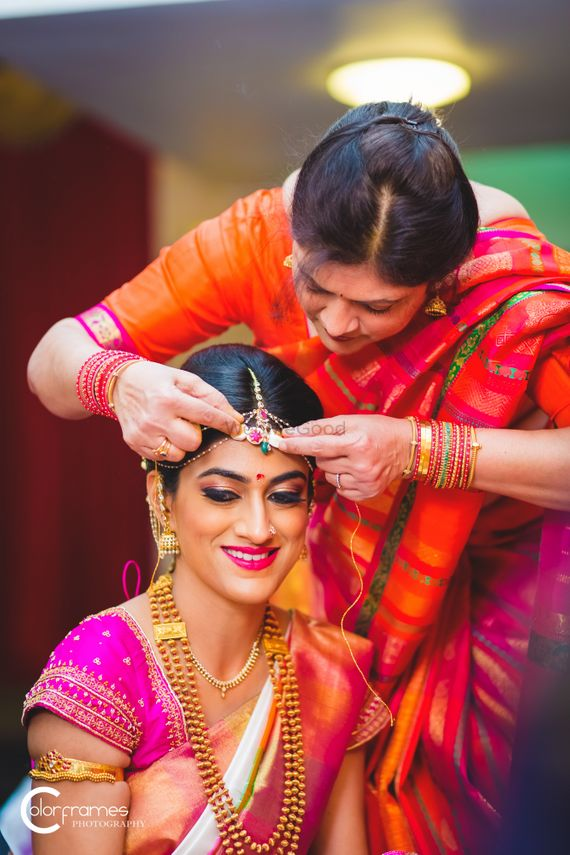 Photo of Mother of the bride adjusting the brides maang tikka