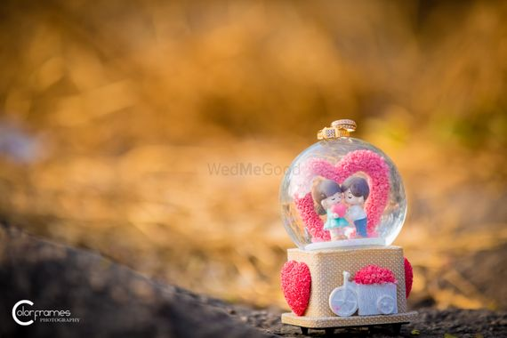 Photo of Engagement Rings on Top of a Cute Snow Globe