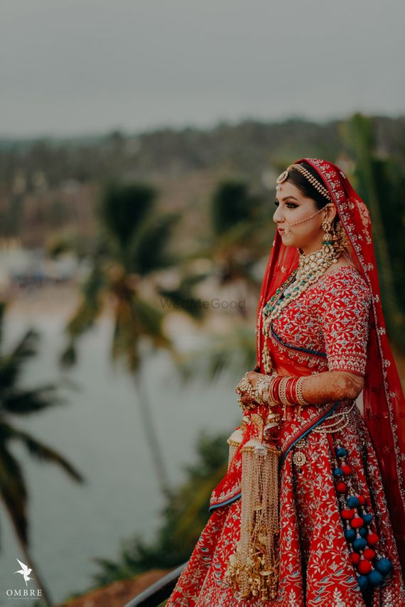 Photo of red and blue bridal lehenga with unique latkans