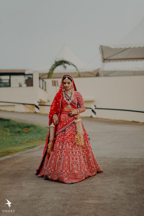 Photo of gold and red embroidered bridal lehenga with kaleere