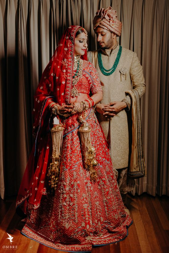 Photo of bride in red and groom in beige with a green necklace